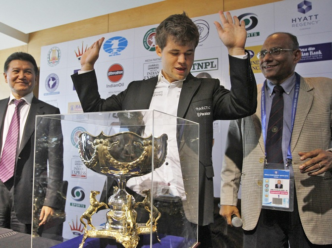 Norway's Magnus Carlsen (C) gestures next to his trophy after clinching the FIDE World Chess Championship in the southern Indian city of Chennai November 25, 2013. Carlsen replaces India's Viswanathan Anand as world chess champion. REUTERS/Babu (INDIA - Tags: SPORT CHESS) - RTX15SEC