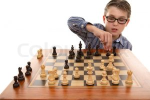 2806520-a-boy-moving-a-chess-piece-on-a-portable-chess-game-table