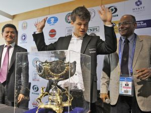 Norway's Carlsen gestures next to his trophy after clinching the FIDE World Chess Championship in Chennai